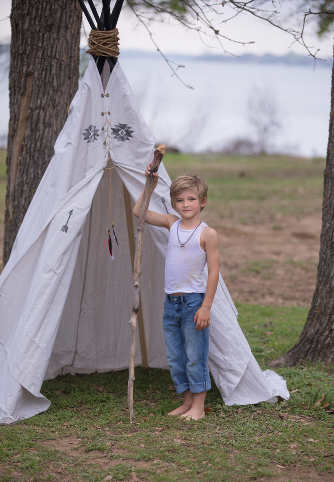 boy playing with walking stick and teepee in portrait in arlington tx