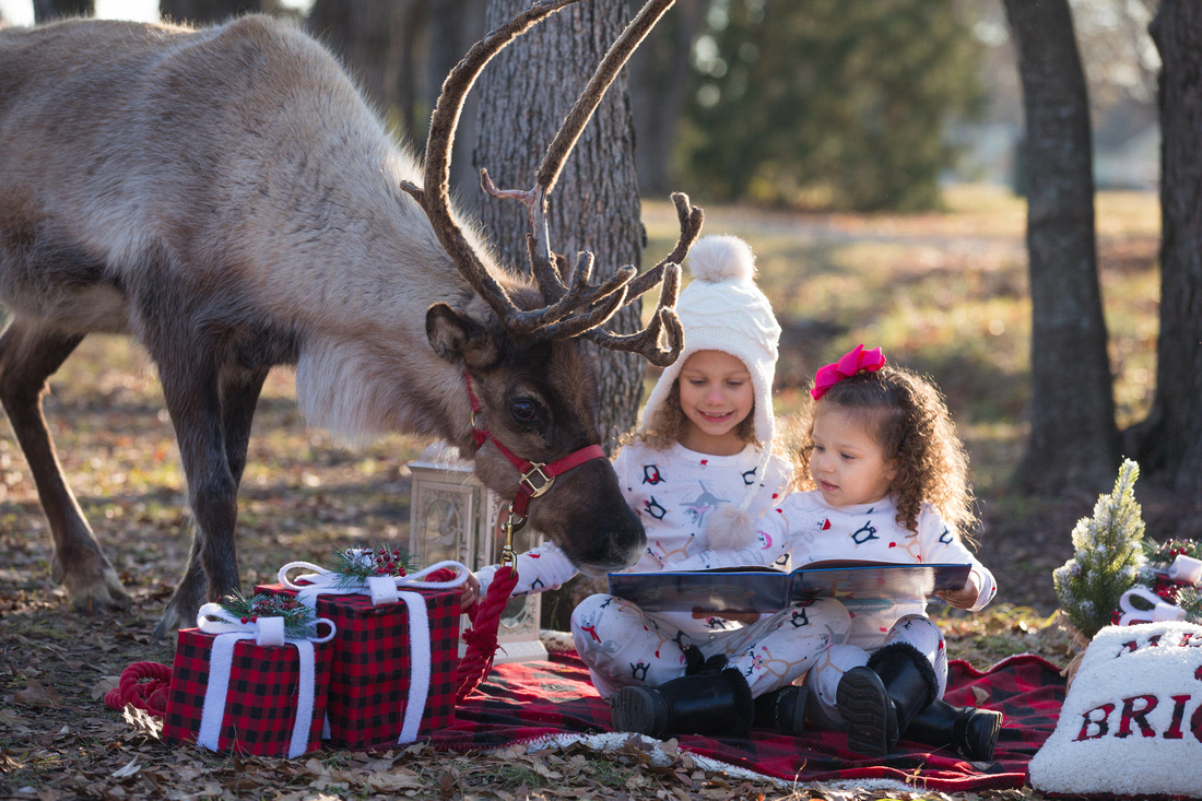 two girls reading a book with a reindeer