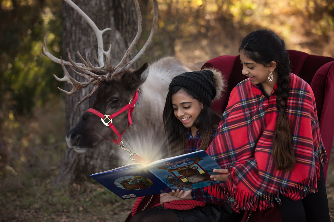 two girls reading with reindeer and book has magic