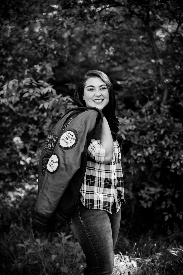 senior girl posing with her letterman jacket in Mansfield tx