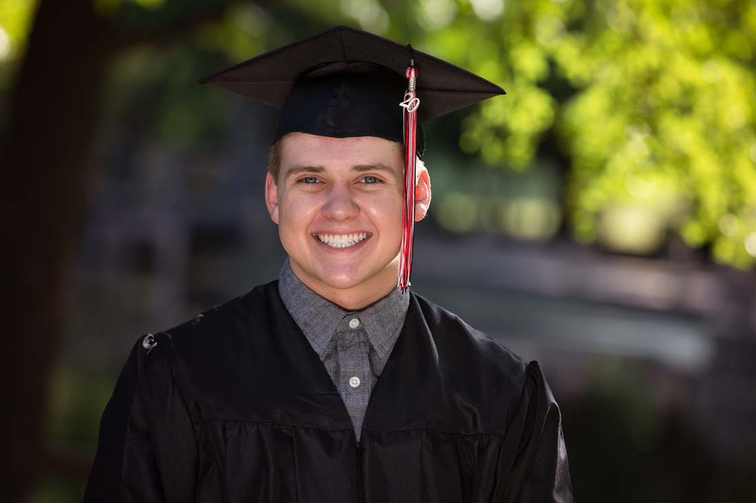 senior boy in cap and gown posing for headshot in fort worth tx